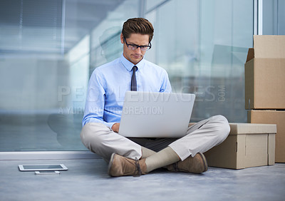 Buy stock photo A young businessman sitting on the floor of an empty office working on a laptop while surrounded by boxes