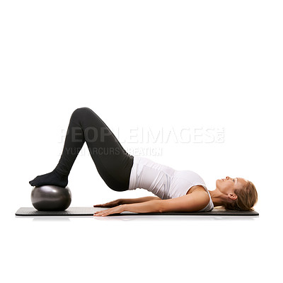 Buy stock photo A young woman using an exercise ball to raise her back into the air - isolated