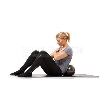 Buy stock photo A young woman doing sit-ups on an exercise ball while isolated on a white background