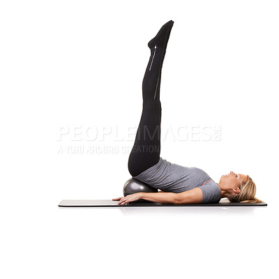 Buy stock photo A young woman lying on an exercise ball and extending straight upwards
