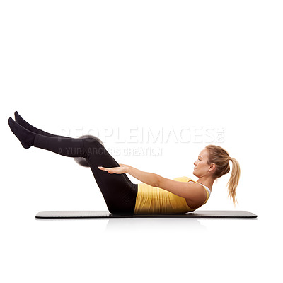 Buy stock photo A young woman doing crunches with an exercise ball while isolated on white
