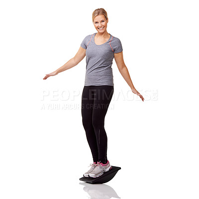 Buy stock photo A pretty young woman exercising on a balance board while isolated on a white background