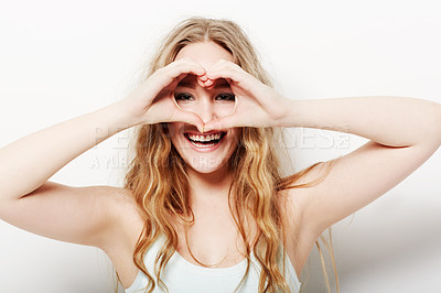 Buy stock photo Smiling young woman making a heart-shape with her hands against a white background