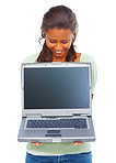 Happy young woman displaying a laptop on white
