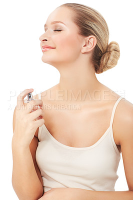 Buy stock photo A beautiful young woman spraying herself with perfume