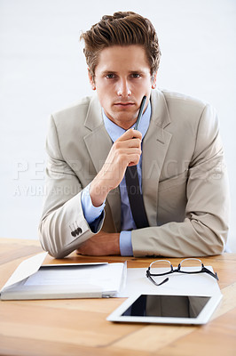 Buy stock photo Portrait of a serious young businessman sitting at his desk with a tablet and paperwork