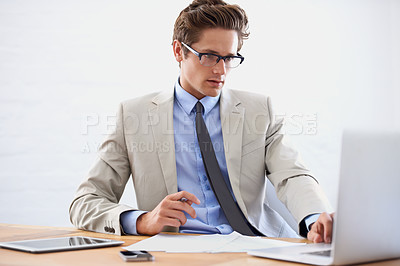 Buy stock photo A handsome young businessman working on his laptop
