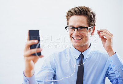 Buy stock photo A handsome young businessman choosing a song from his smartphone's playlist