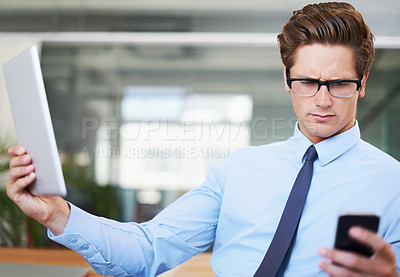 Buy stock photo A young businessman reading a text message while holding a digital tablet