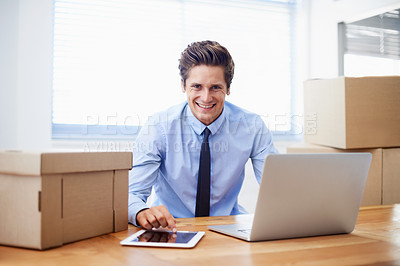 Buy stock photo A young man sitting in his new office surrounded by moving boxes
