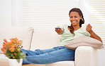 Young lady enjoying cup of coffee while holding a television rem