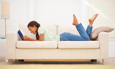 Buy stock photo Young African American female lying on the couch while reading a book
