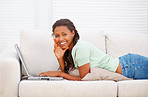 Charming young woman lying on the sofa using a laptop