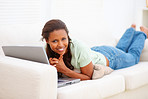 Pretty young woman lying on the sofa using a laptop