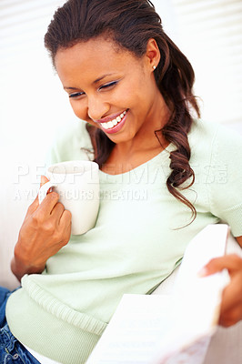 Buy stock photo Happy African American woman reading a book, having a cup of tea