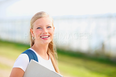 Buy stock photo Cute young female student holding a folder, smiling outdoors