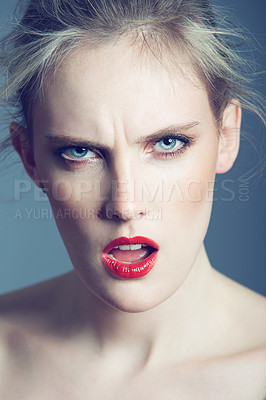 Buy stock photo Studio shot of a beautiful young woman looking angry against a gray background