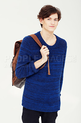 Buy stock photo A confident young student wearing a backpack over his shoulder while posing for a studio shoot