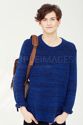 Buy stock photo A confident young student wearing a backpack over his shoulder with his hands in his pockets