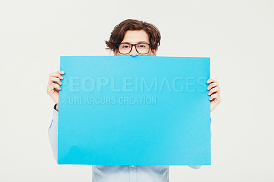 Buy stock photo A young man holding a blue placard up for your copyspace