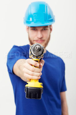 Buy stock photo Portrait of a young man wearing a hardhat and holding a power drill