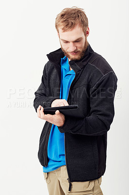 Buy stock photo An unshaven young man working on a digital tablet