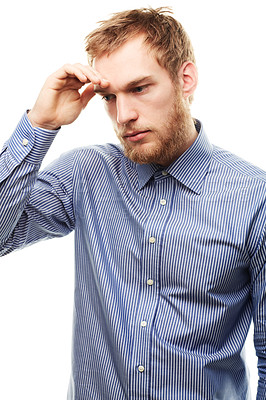 Buy stock photo A worried looking young man touching his forehead isolated on white