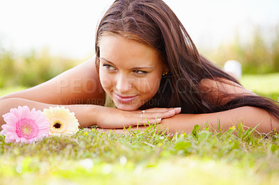 Buy stock photo Cute young female lying on grass with some flowers looking away dreamily - copyspace
