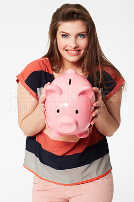 Buy stock photo A beautiful young woman holding a piggy bank