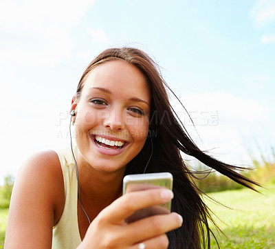 Buy stock photo Portrait of a happy young female listening to music while relaxing at the park