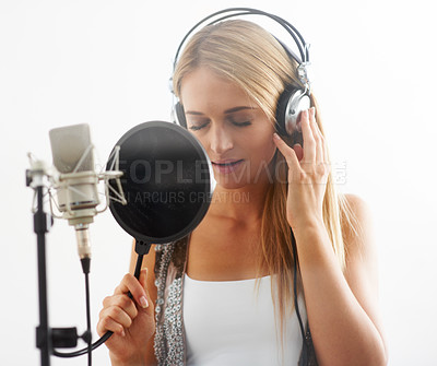 Buy stock photo A lovely young singer recording a track while wearing headphones