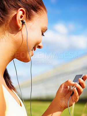 Buy stock photo Happy young female listening to music outdoors on a sunny day - copyspace