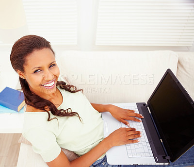 Buy stock photo Top view of a happy African American young woman using a laptop at home