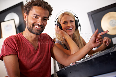 Buy stock photo Two young music producers working on their mixing desk with gold albums in the background - portrait