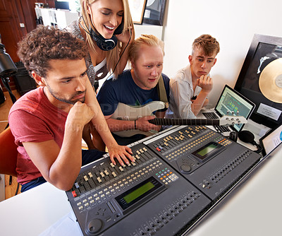 Buy stock photo Four young music producers sitting in front of a mixing desk in their studio