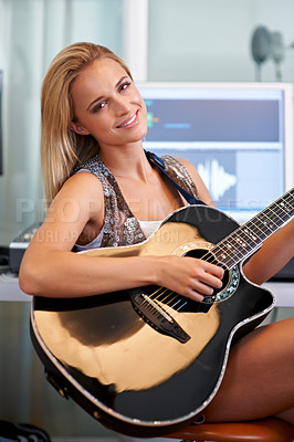 Buy stock photo A beautiful blonde guitarist sitting in a recording studio with her instrument