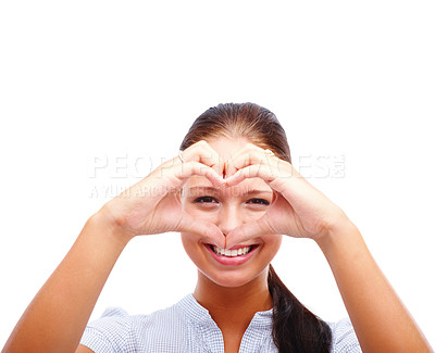Buy stock photo Portrait of a young woman making a heart shape sign with her hands on white