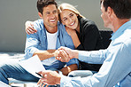 Happy young couple shaking hand with agent