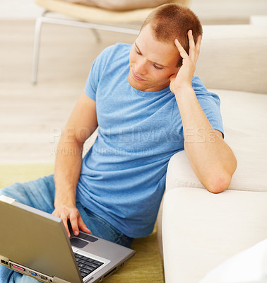Buy stock photo Portrait of a thoughtful guy working on a laptop at home