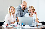 Three business people smiling and working at office