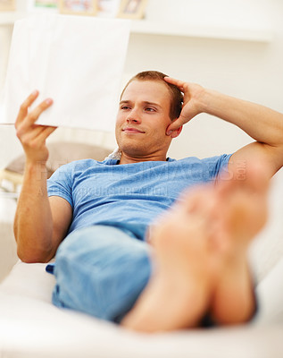 Buy stock photo Handsome young guy reading a novel while relaxing on the couch at home