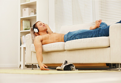 Buy stock photo Handsome young man relaxing shirtless on the sofa listening to peaceful music