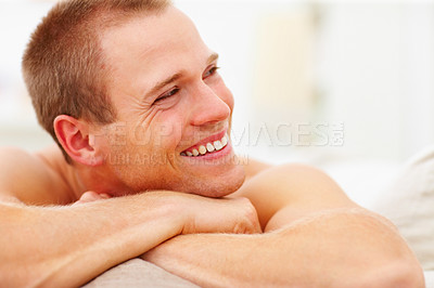 Buy stock photo Closeup of a happy young man relaxing on the couch at home, looking away