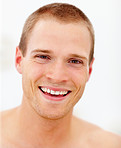 Portrait of a handsome young man smiling over white background