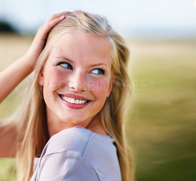 Buy stock photo Pretty young blond female smiling, playing with her hair