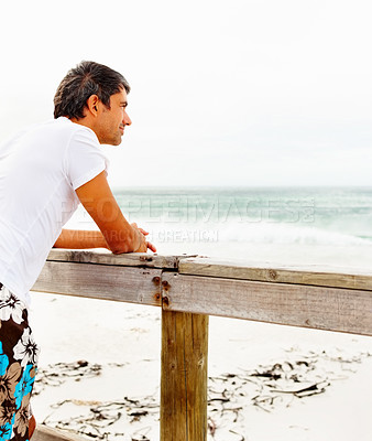 Buy stock photo Mature man relaxing on a wooden railing looking at the sea