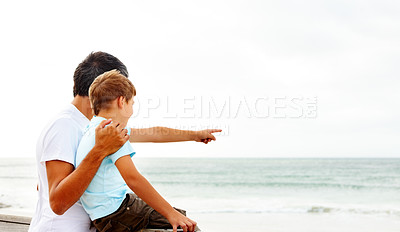 Buy stock photo Father and son on a beach vacation together, son pointing towards the sea