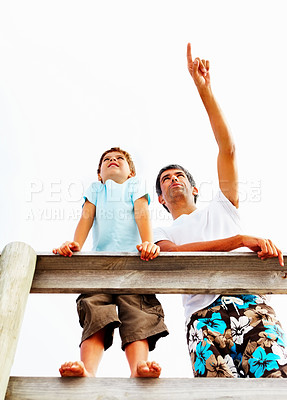Buy stock photo Upward view of a father and son standing on a wooden railing, father pointing into bright white copyspace