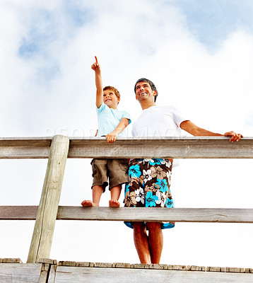 Buy stock photo Upward view of a father and son standing on a wooden railing, son pointing out at something