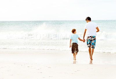 Buy stock photo Rear view of a father and son holding hands walking towards the sea